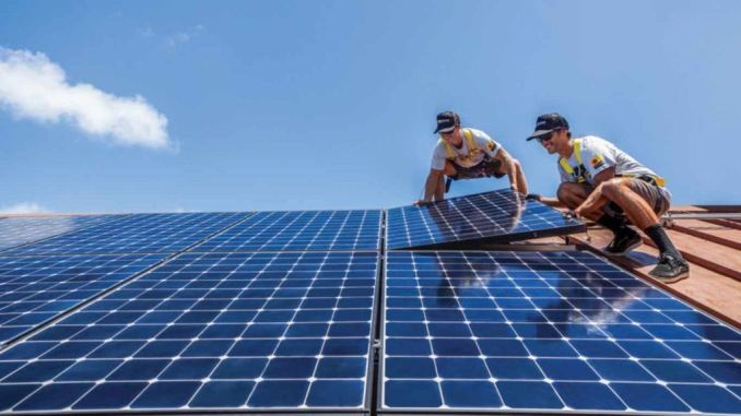 two men installing solar panels on a rising sun customer with smiles on their faces