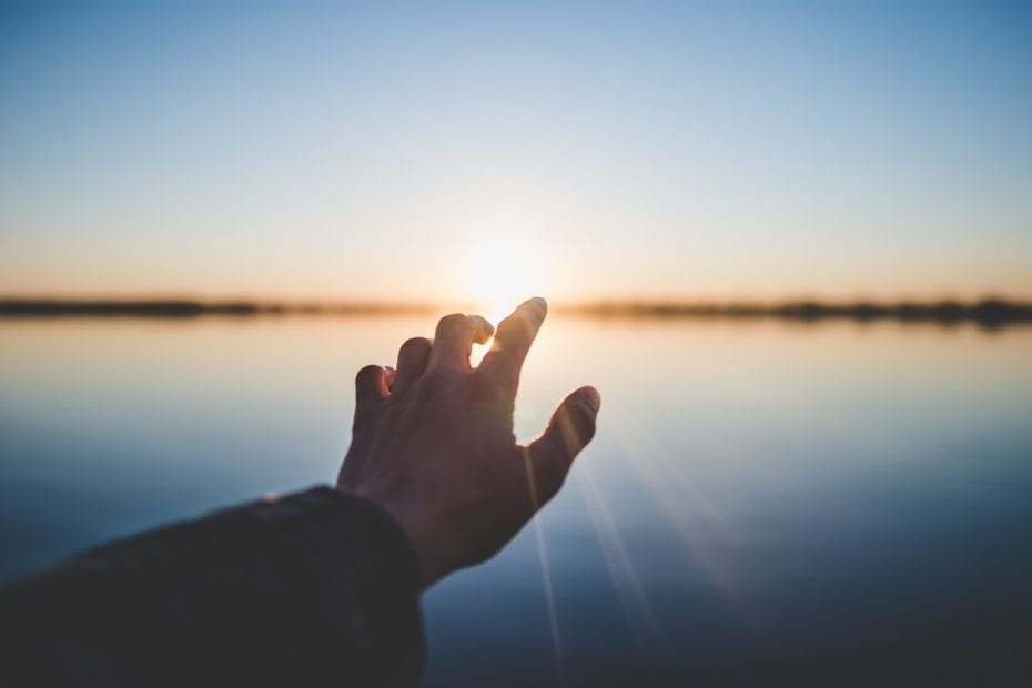 person extending their hand toward the sun near a body of water.