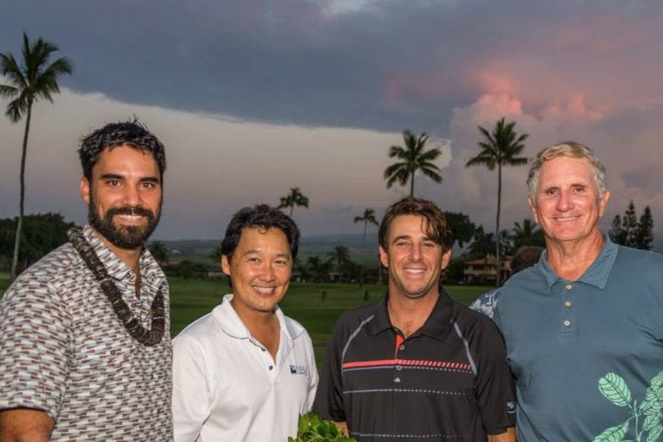 four men standing at the golf course with palm trees and clouds in background