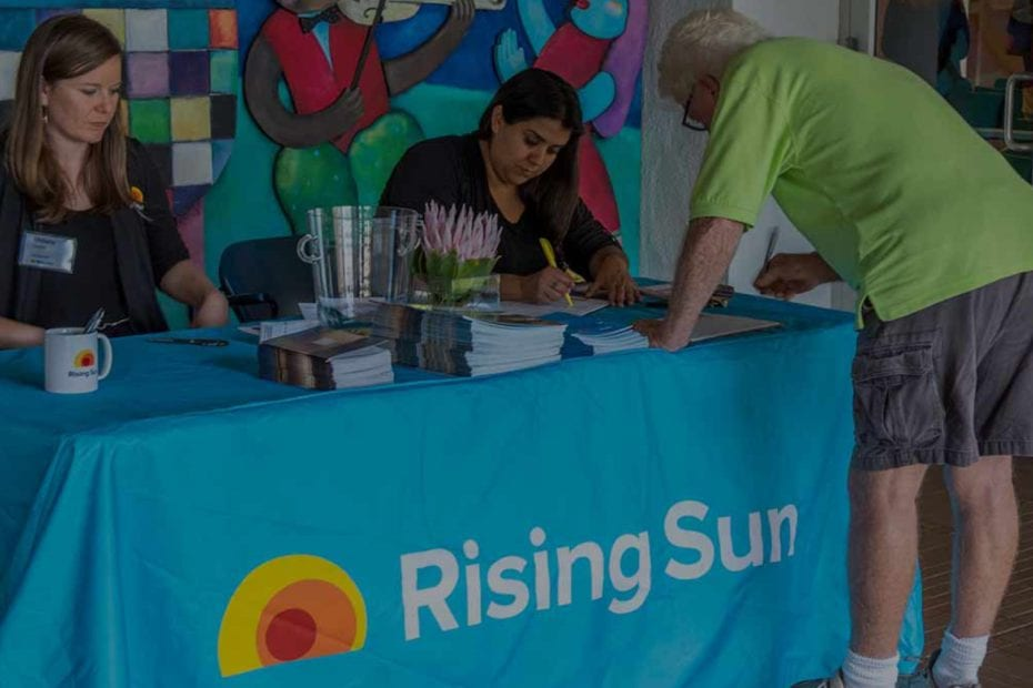 people signing up for rising sun information siting at a table