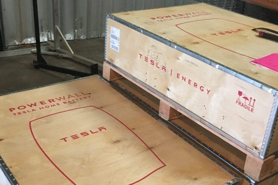 tesla powerwalls in their shipping boxes ariving at rising sun solars warehouse