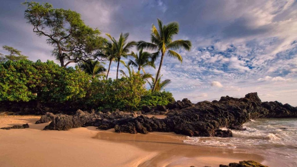 sunset picture from cove beach on Maui in Makena with rocks and ocean crashing up on shore