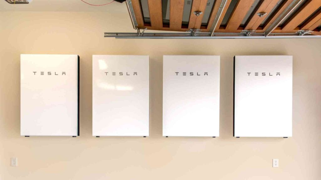 four tesla powerwalls installed on a wall in a Hawaiian home garage