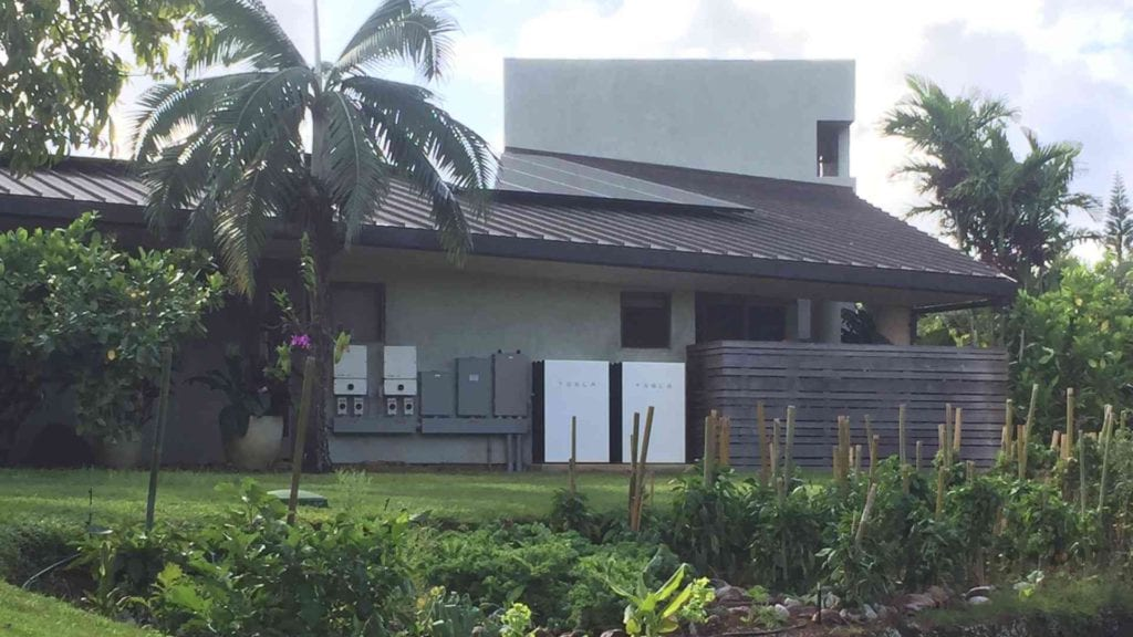 tesla solar panels and tesla power wall on a home in hawaii with garden